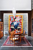 Fine wood dining table and chairs in front of gold frame picture with Asian woman motif on light brick wall