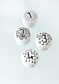 White porcelain knobs decorated with black patterns and numbers