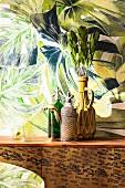 Vase und Sodaflaschen auf einer Leo-Kommode vor Dschungeltapete