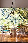Dining table with various chairs in front of a jungle wallpaper