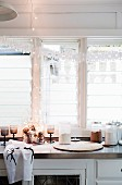 Paper garland and fairy lights in front of kitchen window and pine cones in decorative glass as Christmas decorations