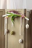 Weißer Kleiderbügel dekoriert mit rosa Blüten und gepunkteten angehängten Ostereiern an Vintage-Paravent