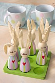 Cute, painted, wooden bunny ornaments with fabric ears on green wooden board with matching sockets