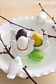 Bird ornaments, budding twigs and colourful Easter eggs in traditional egg cups arranged on white, china plate