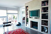 Concrete partition with various apertures for books, TV and gas fireplace in open-pan interior with view of terrace