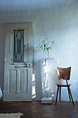 Vintage door leaning against wall, plant stand and retro wooden chair
