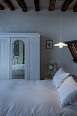 White wardrobe with mirrored panel next to double bed below rustic wood-beamed ceiling