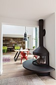 Black log burner with semicircular fireplace bench in front of open doorway in open-plan interior with dining area in background