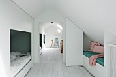 White wooden floor and row of alcoves under sloping ceiling in converted attic