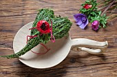 Spring place setting with heart-shaped bundle of bilberry stalks and red anemone flower