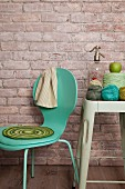 Crocheted seat pad on turquoise chair and crochet yarn and soda siphon on vintage stool against brick wall