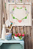 Vintage wooden tray embroidered with heart motif on board wall