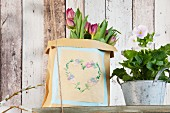Vintage-style heart motif embroidered on paper bag and flowers on old wooden shelf