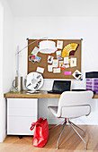 Pin board above desk with white upholstered chair