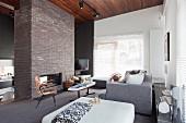 Wohnraum mit Polstertisch und gemütlicher Couch gegenüber offenem Kamin in Klinkermauerstück