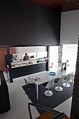 Blick von oben auf weissen Esstisch und Klassiker Schalenstühle, gegenüber offene Küche mit Frau hinter Theke