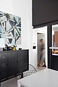 Black sideboard below modern artwork in open-plan dining area with black steel pillar