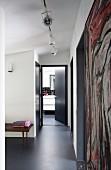 Dark grey epoxy resin floor in foyer with open bathroom door at far end