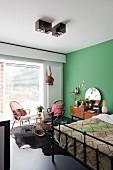 Schwarzes Metallbett vor grüner Wand und Rattanstühle vor Fenster in Schlafzimmer mit Retro-Flair