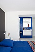 Royal-blue bed linen on double bed against black wall and white floating washstand on blue mosaic-tiled wall in ensuite bathroom