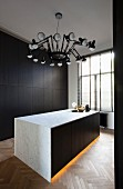 Monolithic counter with indirect lighting in plinth and marble body below pendant lamp with multiple cantilever arms