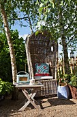 Comfortable beach chair and garden table below birches in secluded corner of garden