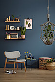 A shelf on a blue wall, a grey chair, a side table, basket and a hanging basket in a living room