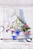 Various summer flowers lying on a tea towel