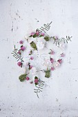 A garland of flowers featuring strawflowers, globa amaranth, corral ferns and wild carrot