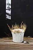 Selbstgebasteltes Windlicht aus Papiermaschee dekoriert mit Ähren und Gräsern