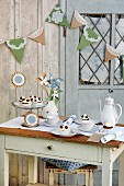 Table set with small cakes and coffee outside wooden shed decorated with bunting