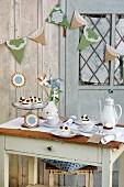Gedeckter Nachmittagstisch mit Küchlein und Kaffee vor Holzhäuschen mit aufgehängter Girlande