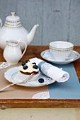 Kaffee und Gebäck auf Tisch im Freien mit nostalgischen Spitzendeckchen dekoriert