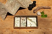 Old box lined with maps, binoculars, unfolded map and natural finds on wooden table