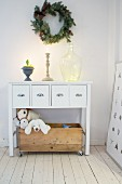 Wreath above white sideboard with wooden crate of toys