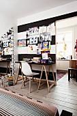 Weißer Klassikerstuhl an Schreibtisch vor aufgehängten Kinderzeichnungen an schwarz-weiß gestreifter Wand mit Durchgang