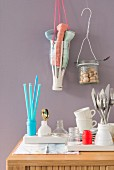Plastic bottles and jam jars hanging on the wall being used as holders for kitchen utensils