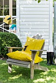 A wooden chair in a garden with a homemade cushion covers made from yellow raincoat material