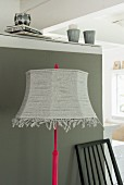 A floor lamp with a homemade lampshade made from strips of jersey