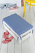 A white footstool with a homemade, checked cover
