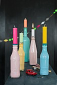 Colourful bottles being used as candleholders
