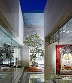 Architectural courtyard of contemporary, Indian house with view of illuminated Hindu shrine through glass wall