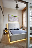 Designer double bed with backlit, grey-upholstered headboard and frame seen through open sliding door in loft-style interior