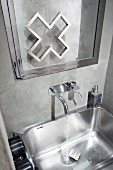 Stainless steel sink with wall-mounted tap and chrome-framed mirror