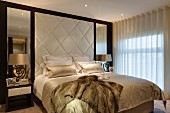 Double bed against elegant upholstered wall panel flanked by mirrors