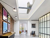 Skylight, brick wall and backlit wall elements in apartment foyer