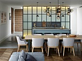 Long dining table and open-plan kitchen with counter in front of industrial-style partition wall