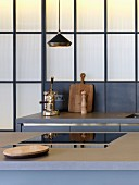 Grey kitchen counter with industrial-style back wall; vintage espresso machine