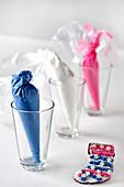 Gläser mit kleinen Süssigkeitentüten als Tischdekoration