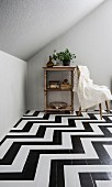 Books and house plant on open-fronted, vintage shelf unit on wooden floor painted with black and white zigzag pattern